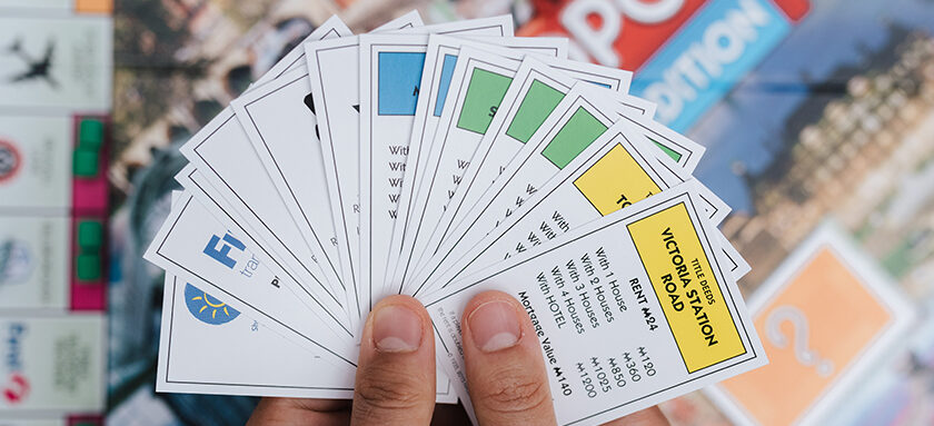 Hands holding monopoly cards