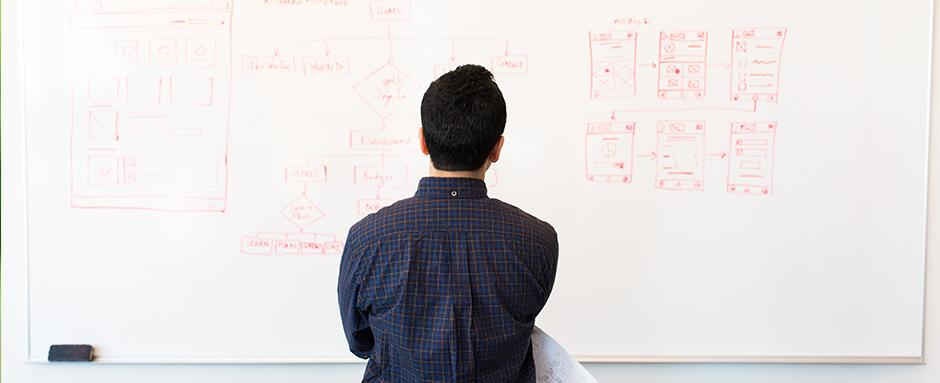 Man staring at whiteboard thinking