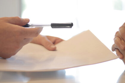 Hands signing mortgage agreement